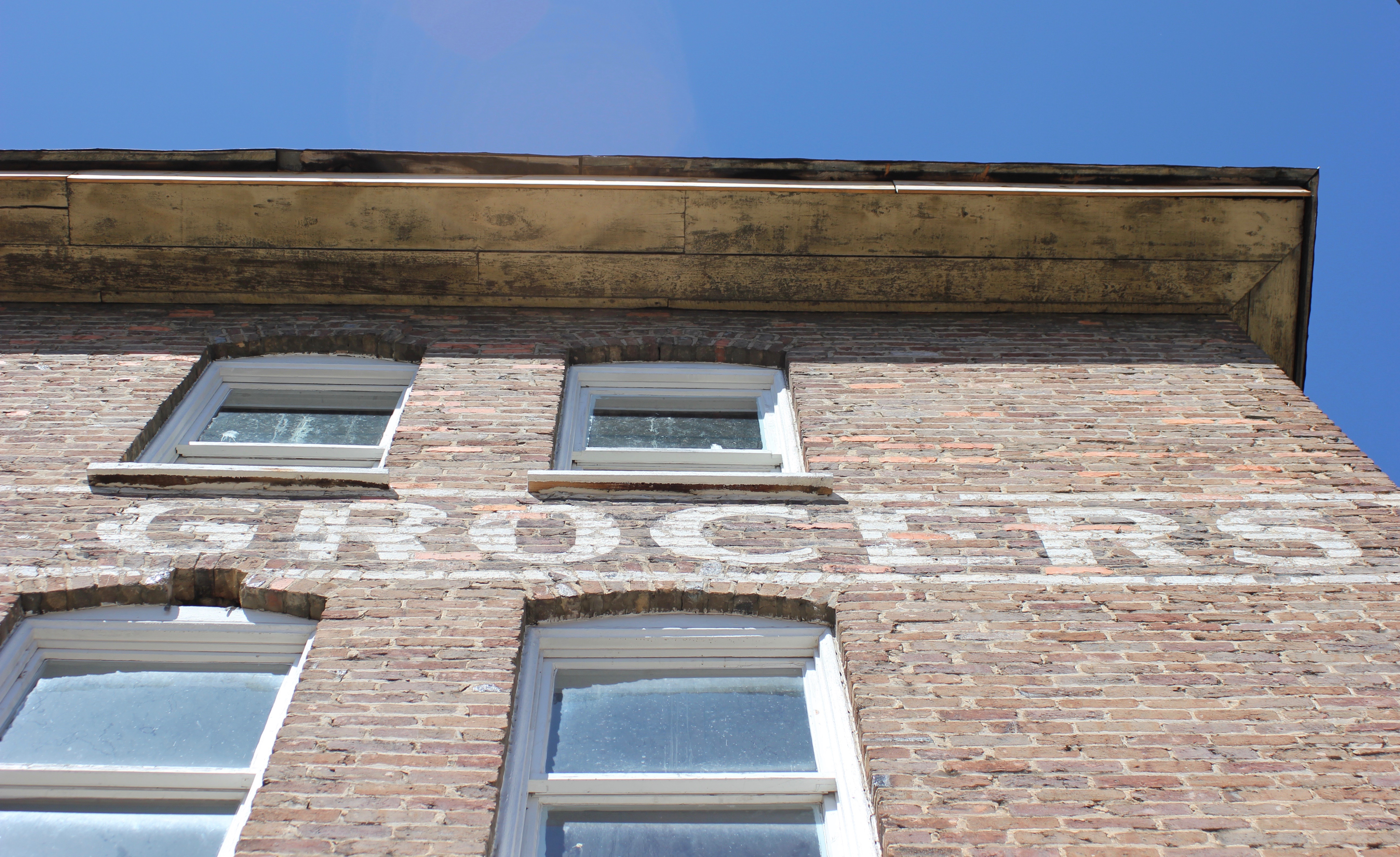 """A brick building with """"Grocers"""" painted on the side."""