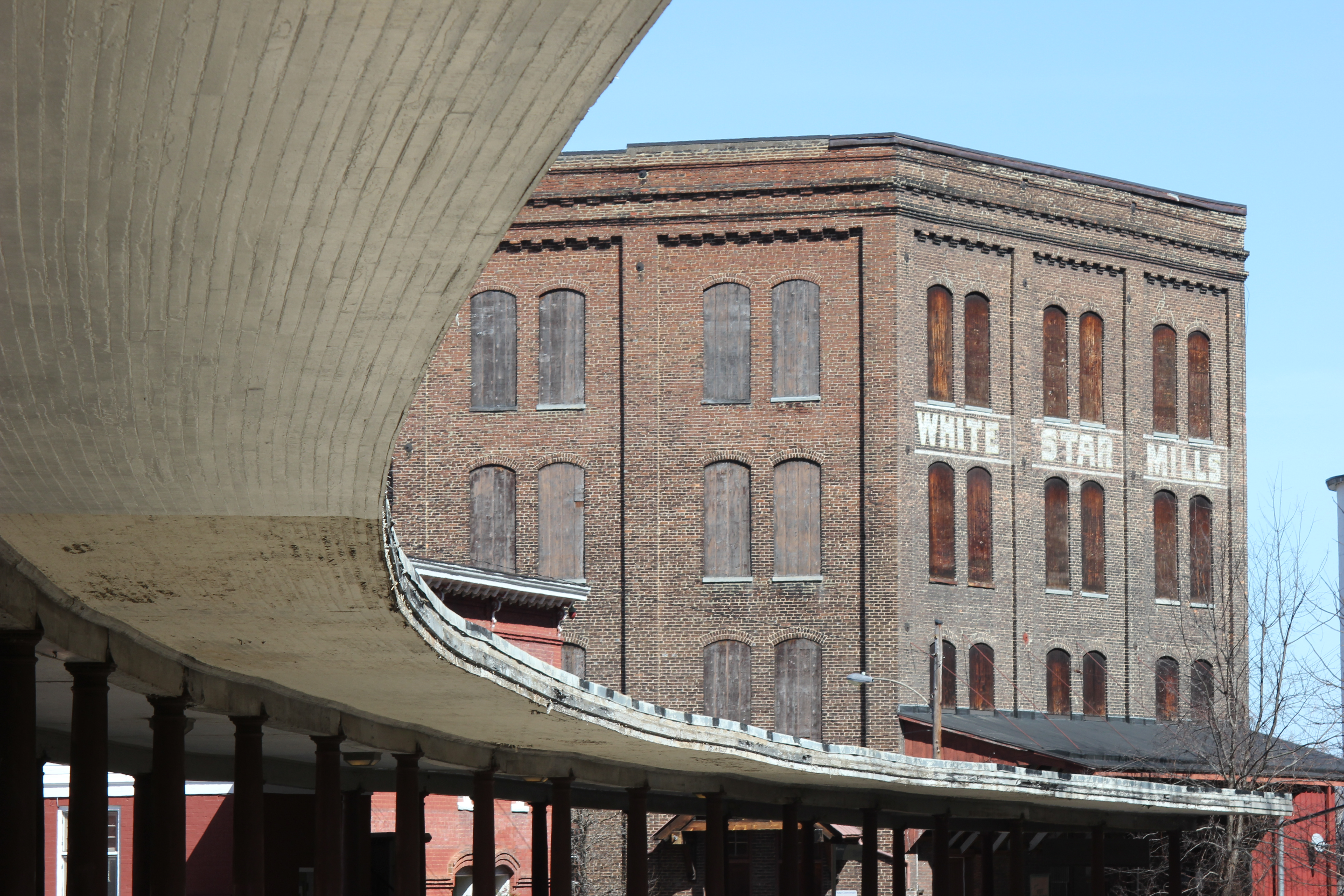 A large former mill in the background and the roof of the train station in the foreground.